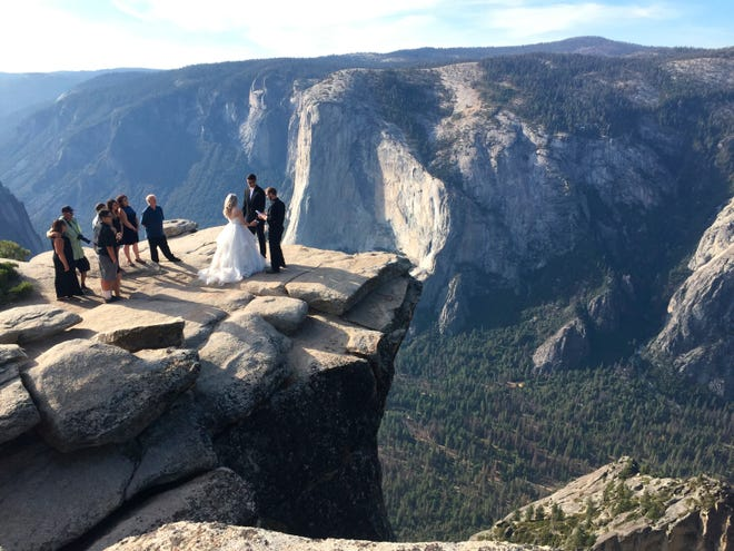 A couple gets married at Taft Point in California's Yosemite National Park on Thursday, Sept. 27, 2018. The viewpoint overlooks Yosemite Valley, including El Capitan, a popular vertical ascent for rock climbers across the globe. (AP Photo/Amanda Lee Myers) ORG XMIT: RPAM103