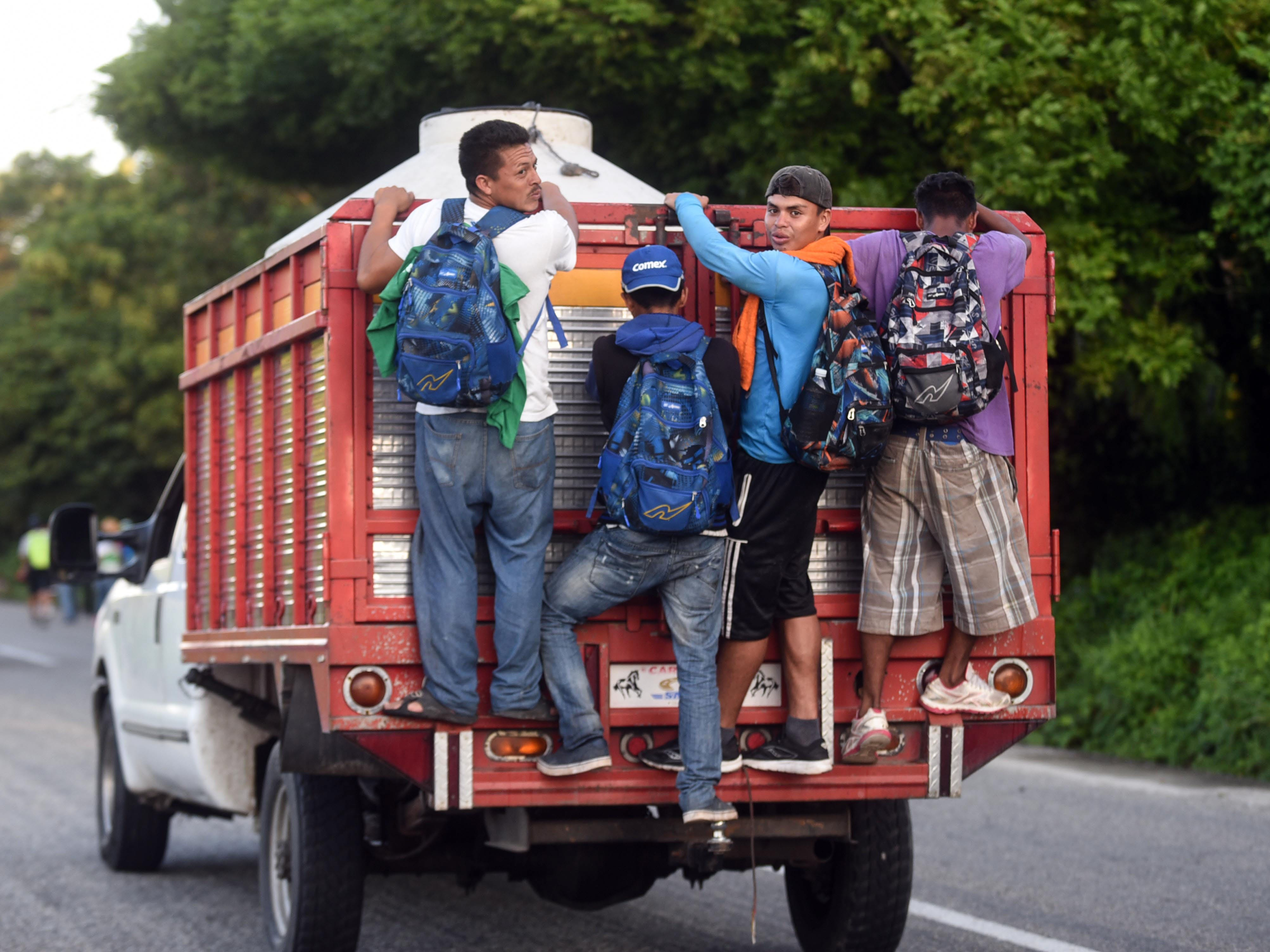 Central American travel standing on the back of a truck in Mapastepec on their way to Pijijiapan Chiapas state, Mexico, Oct. 25, 2018.