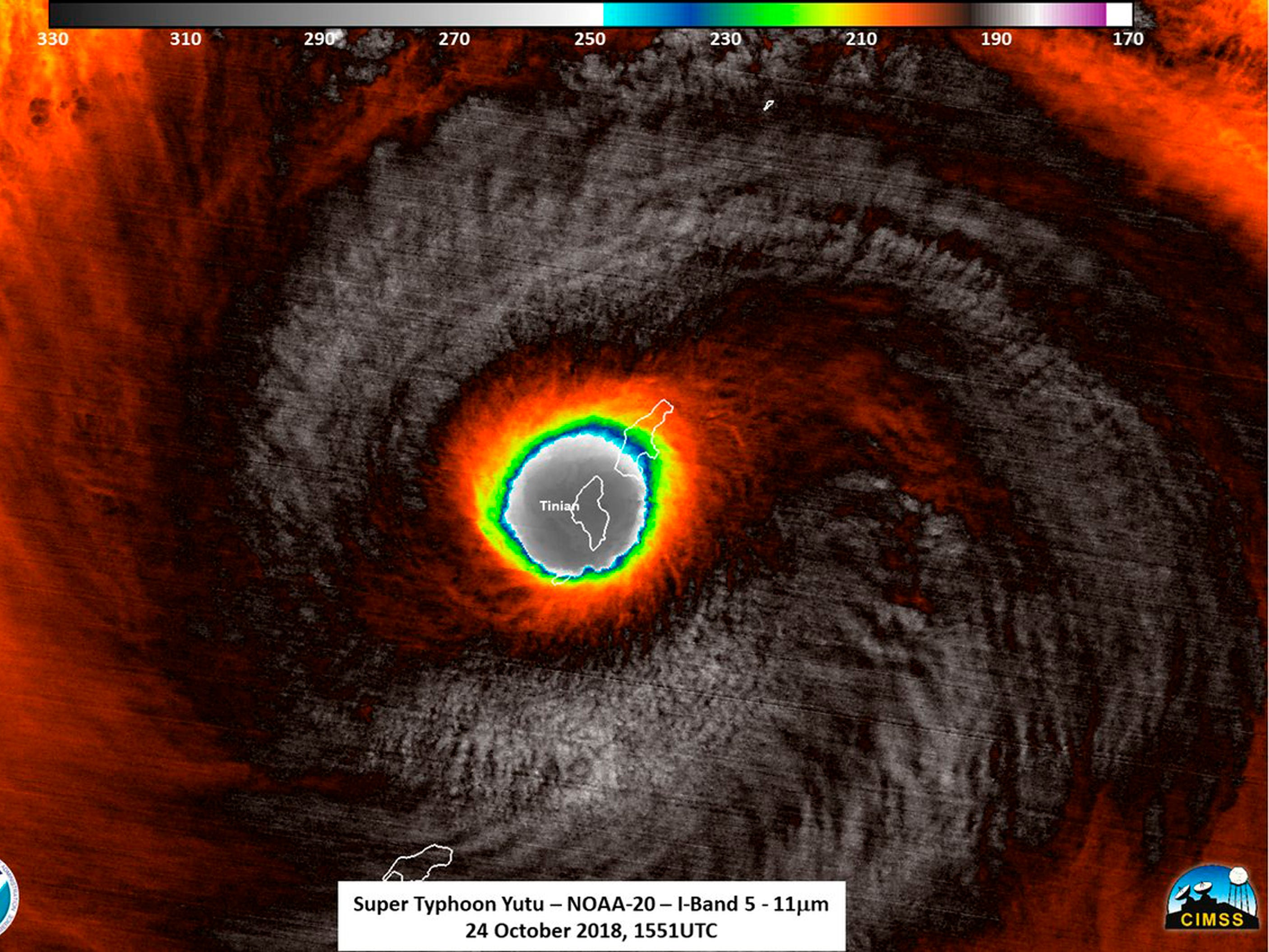 This false-color satellite image provided by the National Oceanic and Atmospheric Administration (NOAA) shows the moment the eye of Super Typhoon Yutu passed over Tinian, one of three main islands in the U.S. Commonwealth of the Northern Mariana Islands, producing damaging winds and high surf Wednesday, Oct. 24, 2018. The National Weather Service in Honolulu says maximum sustained winds of 180 mph (290 kph) were recorded around the eye of the storm, which passed over Tinian island and Saipan early Thursday morning local time. Waves of 25 to 40 feet (6 to 12 meters) are expected around the eye of the storm.
