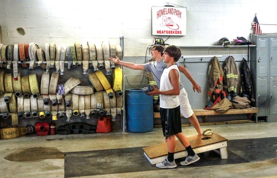 Dylan McCullough tosses a bean bag while Josh Tanner waits his turn at the Homeland Park fire station, during their Independence Day celebration event in 2013.