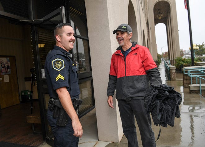 Cpl. Jonathan Dickerson helps Dan Litten of Anderson at City Hall in Anderson. Dickerson is Anderson Police Department's officer of the year.
