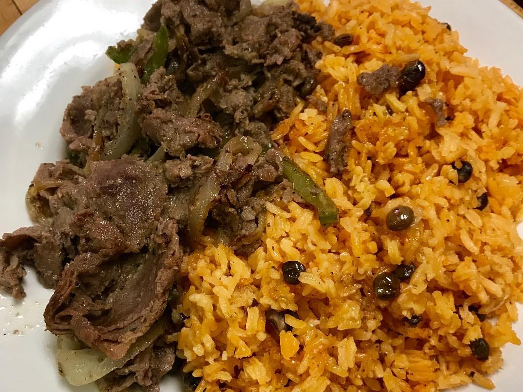 At Ada's Gojjo, pepper and onions steak with rice and gandules, or pigeon peas.