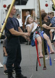 Jackson Police Dept.'s annual National Night Out, American's Night Out against Crime, Tuesday, August 7, 2007. Jackson patrolman, Wayne Olejarz, watches as Christina Mendes, 6, of Jackson, tries her hand on the apparatus used to rescue people from confined spaces. JACKSON - 08/07/07 - -328627 - STAFF PHOTO/MARY FRANK