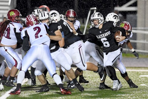 North Buncombe quarterback Caden Higgins attempts to make his way around the Asheville defense during their game at North Buncombe High School on Oct. 25, 2018. The Cougars defeated the Blackhawks 28-19.
