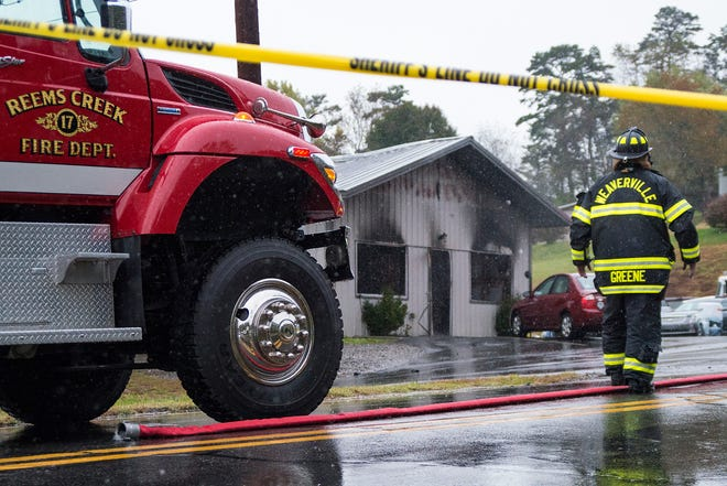 A firefighter walks past the charred front of Weaverville Tire and Wheel off Old Mars Hill Highway in Weaverville on Friday morning. Republican sheriff candidate Shad Higgins owns the shop.