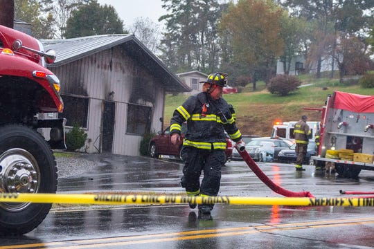 A Weaverville fire fighter begins rolling up a hose after the flames that engulfed Weaverville Tire and Wheel early Friday were extinguished. The business is owned by Republican sheriff candidate Shad Higgins.