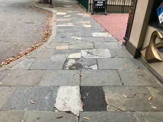The sidewalks on Haywood Street in front of Jewels That Dance and the Pack Memorial Library are a patchwork of concrete and asphalt repairs.