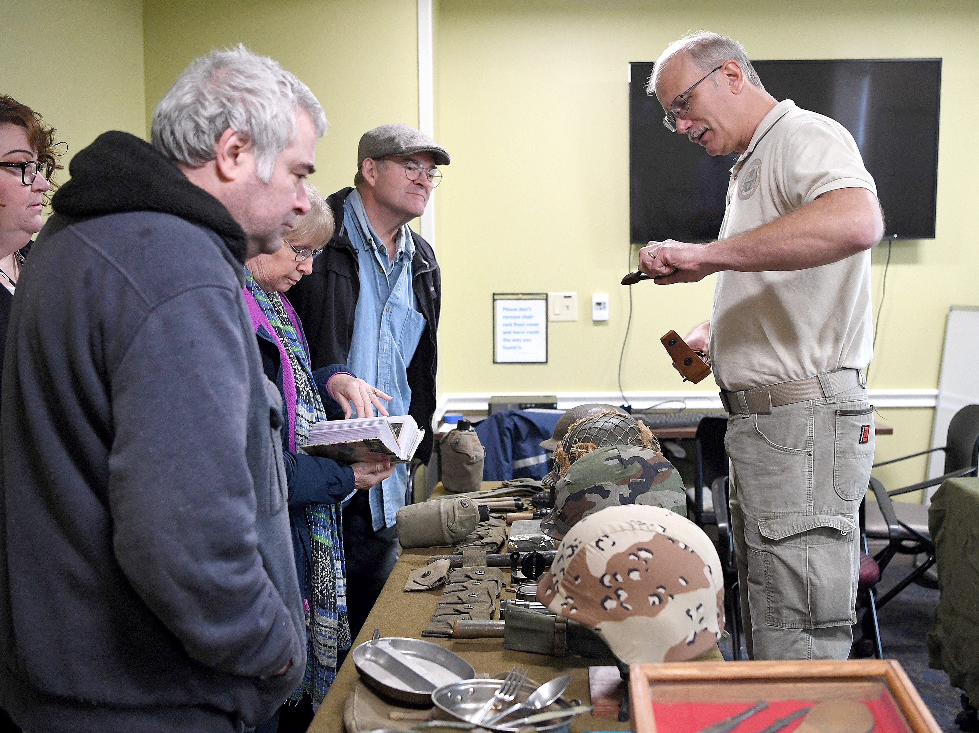 Tom Bugala, curator of the WNC Military History Museum, shows off part of his collection during a ceremony celebrating the opening of the Veterans Hope and Recovery Center on the campus of the Charles George VA Medical Center on Oct. 26, 2018.