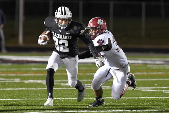 North Buncombe's Wesley Parran outruns Asheville's Ben Scott during their game at North Buncombe High School on Oct. 25, 2018. The Cougars defeated the Blackhawks 28-19.