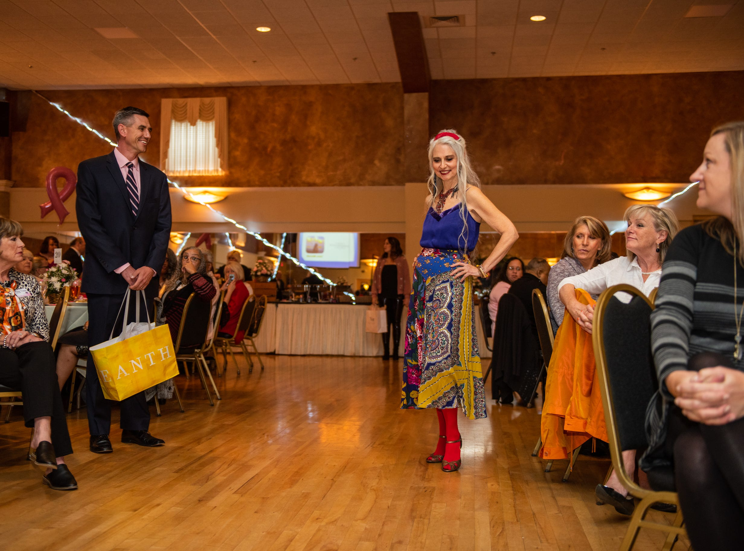 Breast cancer survivor Laura Miklowitz of Hendersonville models an outfit at the Here's Hope Fashion Show fundraiser for the Hope Chest for Women on Oct. 20, 2018, at the Asheville Event Centre.
