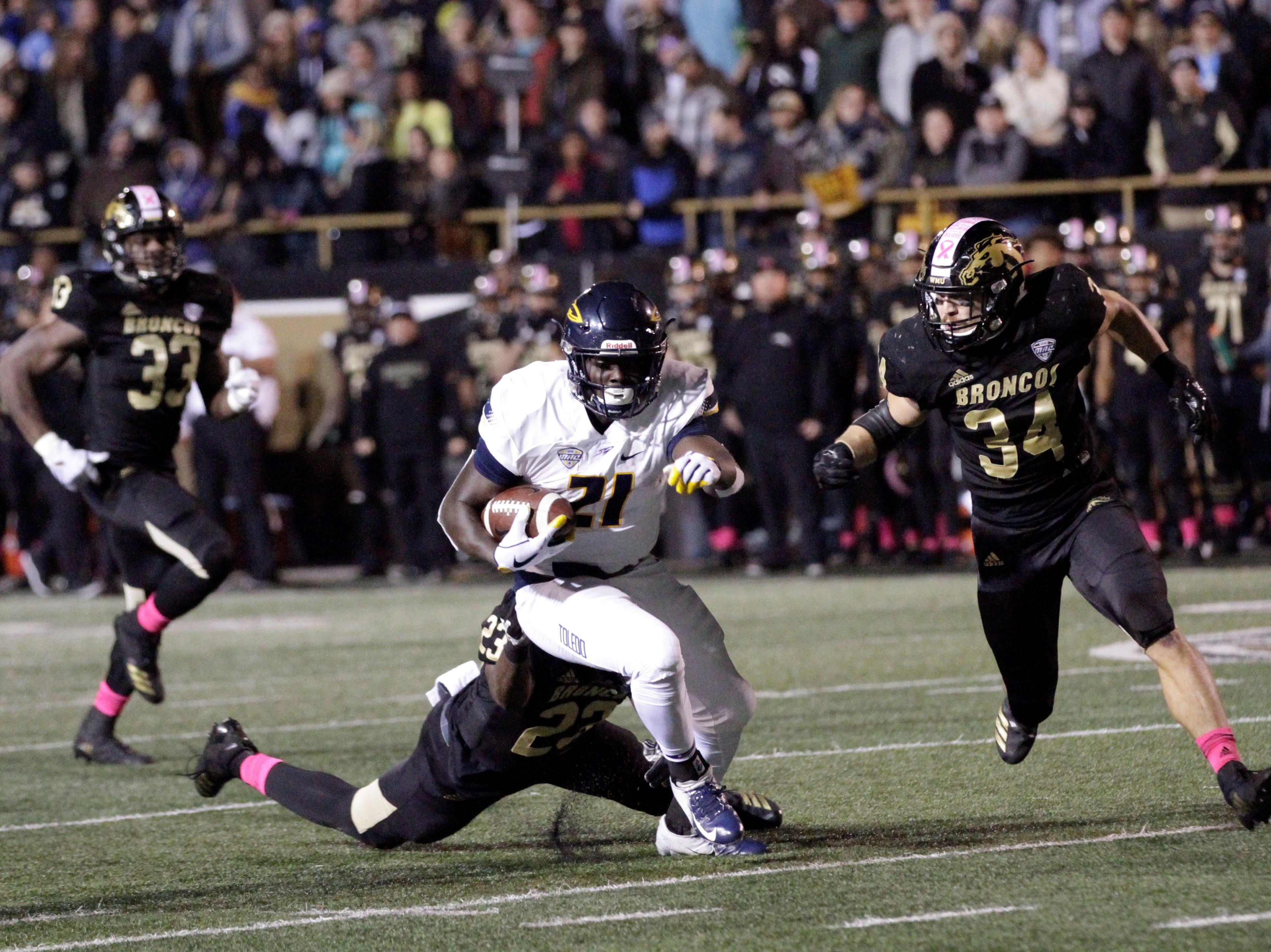 Toledo running back Shakif Seymour (21) attempts to break free from Western Michigan linebacker Treshaun Hayward at Waldo Stadium in Kalamazoo on Thursday, October 25, 2018.