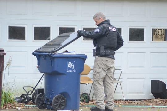 Battle Creek Police Department Lt. Matt Robinson checks trash containers outside an Emmett Township home.