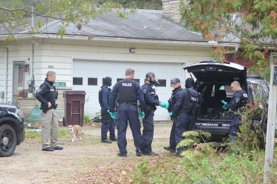 Officers prepare to search an Emmett Township home Friday.