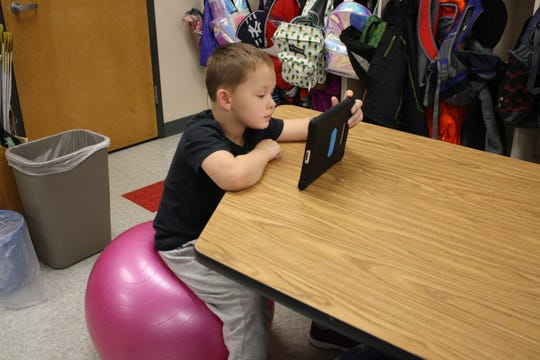 Chenango Forks Elementary School second grader Jayden Paoier, 7, reads while sitting on a yoga ball in Jessica McBreen's classroom on Oct. 26.