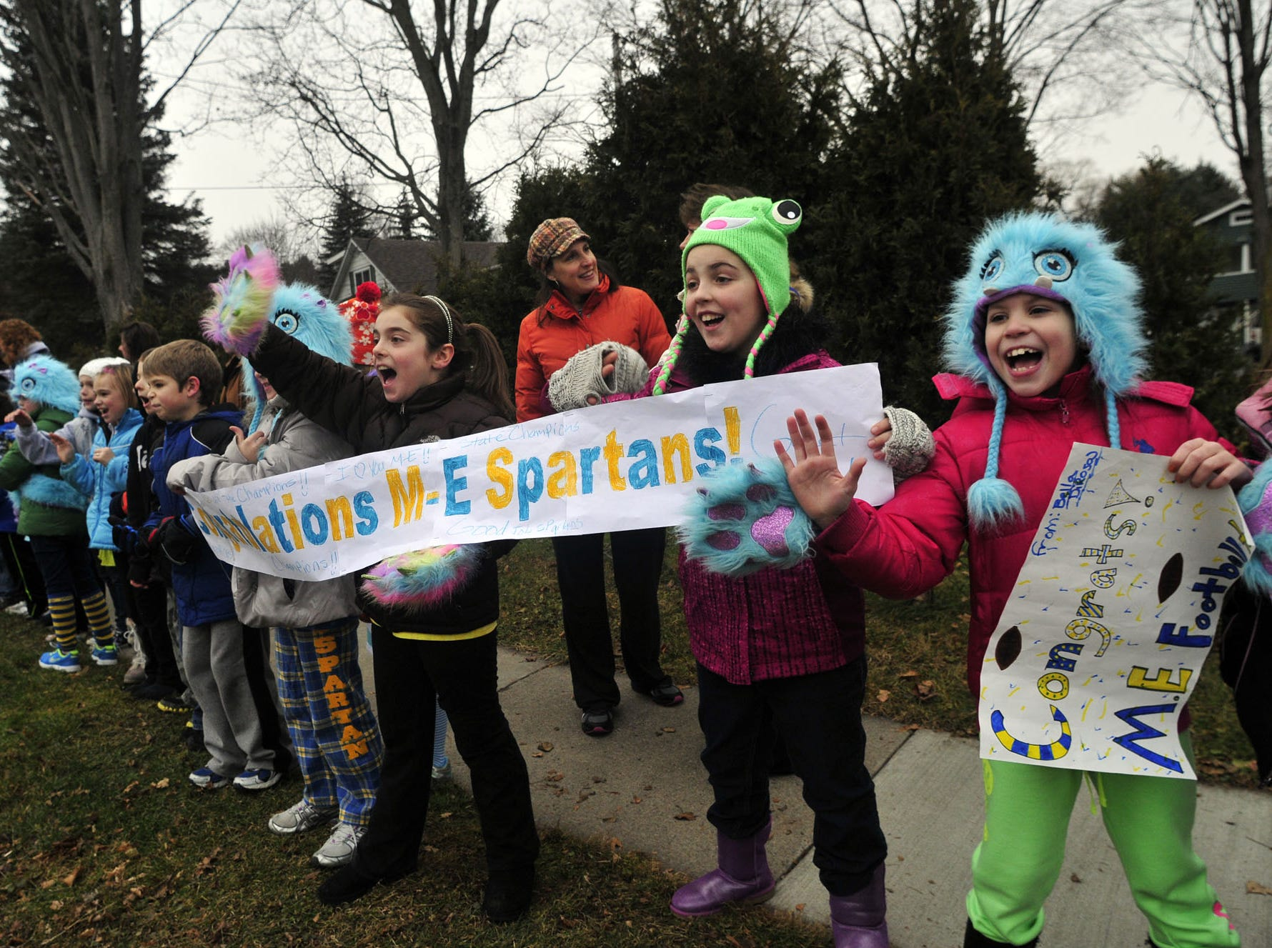 Young Maine-Endwell fans line up at a parade Friday to congratulate the Spartans football team for winning the 2012 state championship.