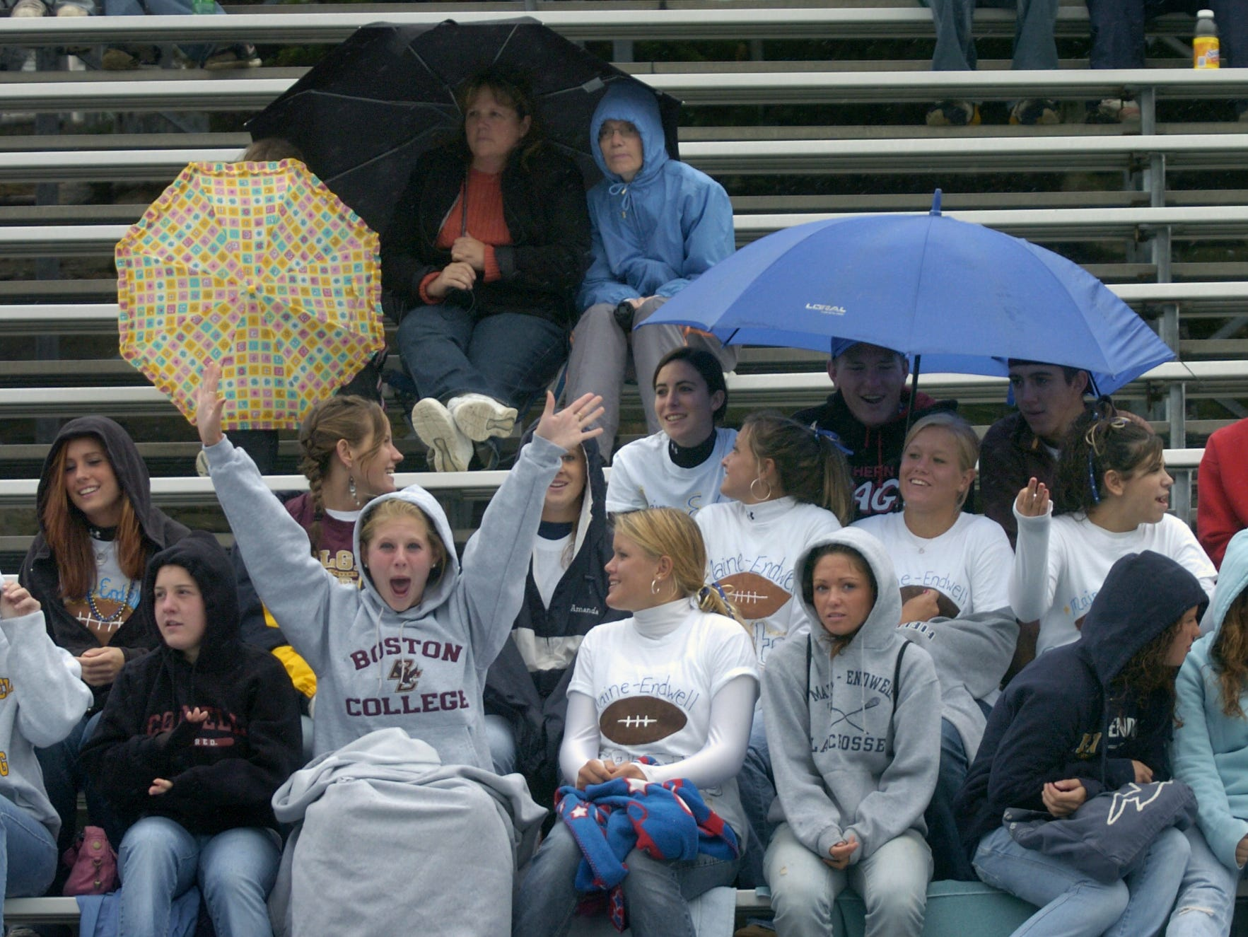 As rain continued to fall Saturday afternoon, football fans take shelter under umbrellas as they watched the Maine-Endwell and Chenango Forks high schools play football at M-E. Kristin Horan, a senior at M-E, cheers her team in  the front row in 2006.