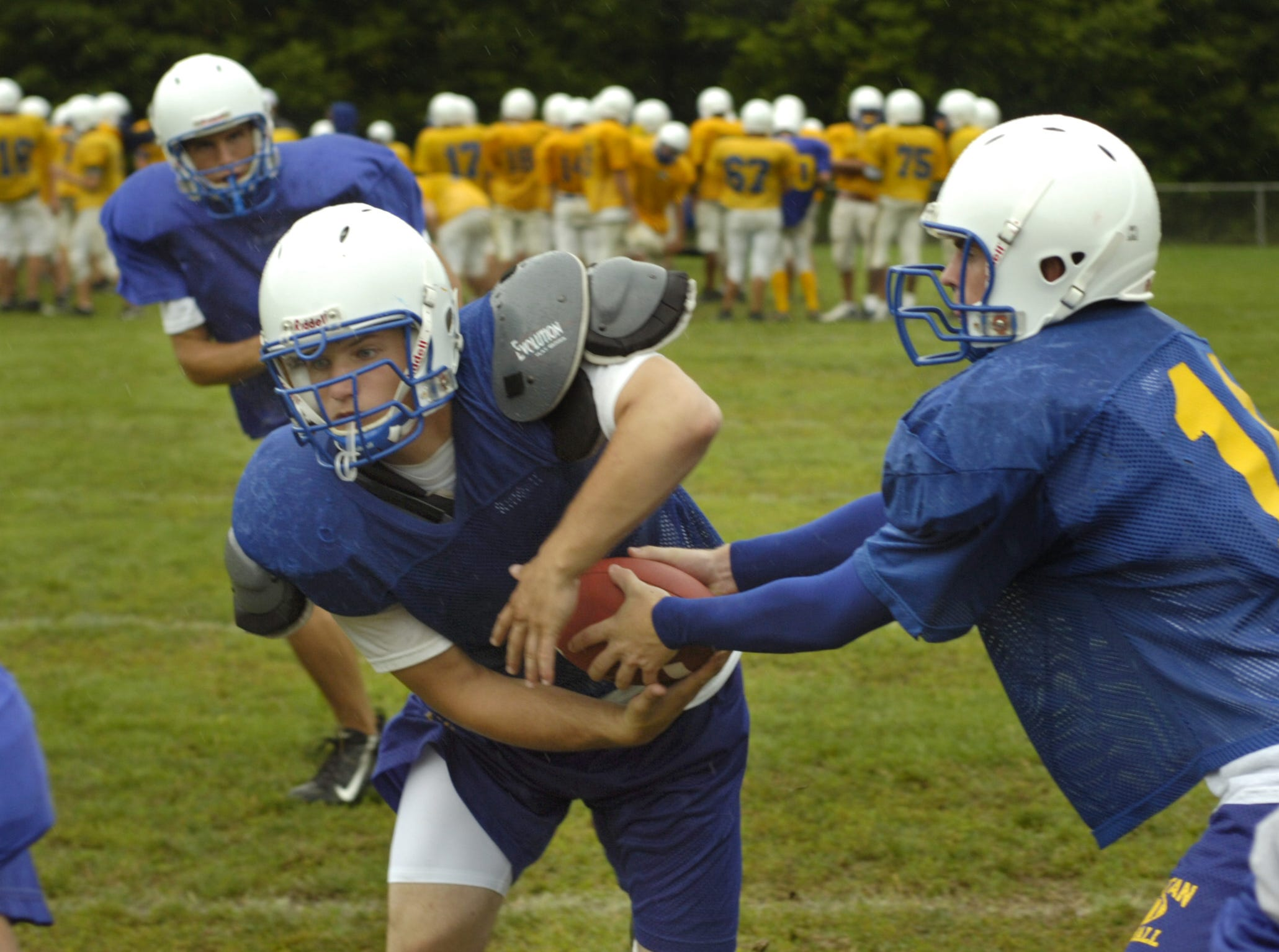 In 2006, running back Madison Trill takes a handoff from quarterback Steve Yeager during preseason drill at Maine-Endwell High School. At upper left Jesse Stevens follows the play.