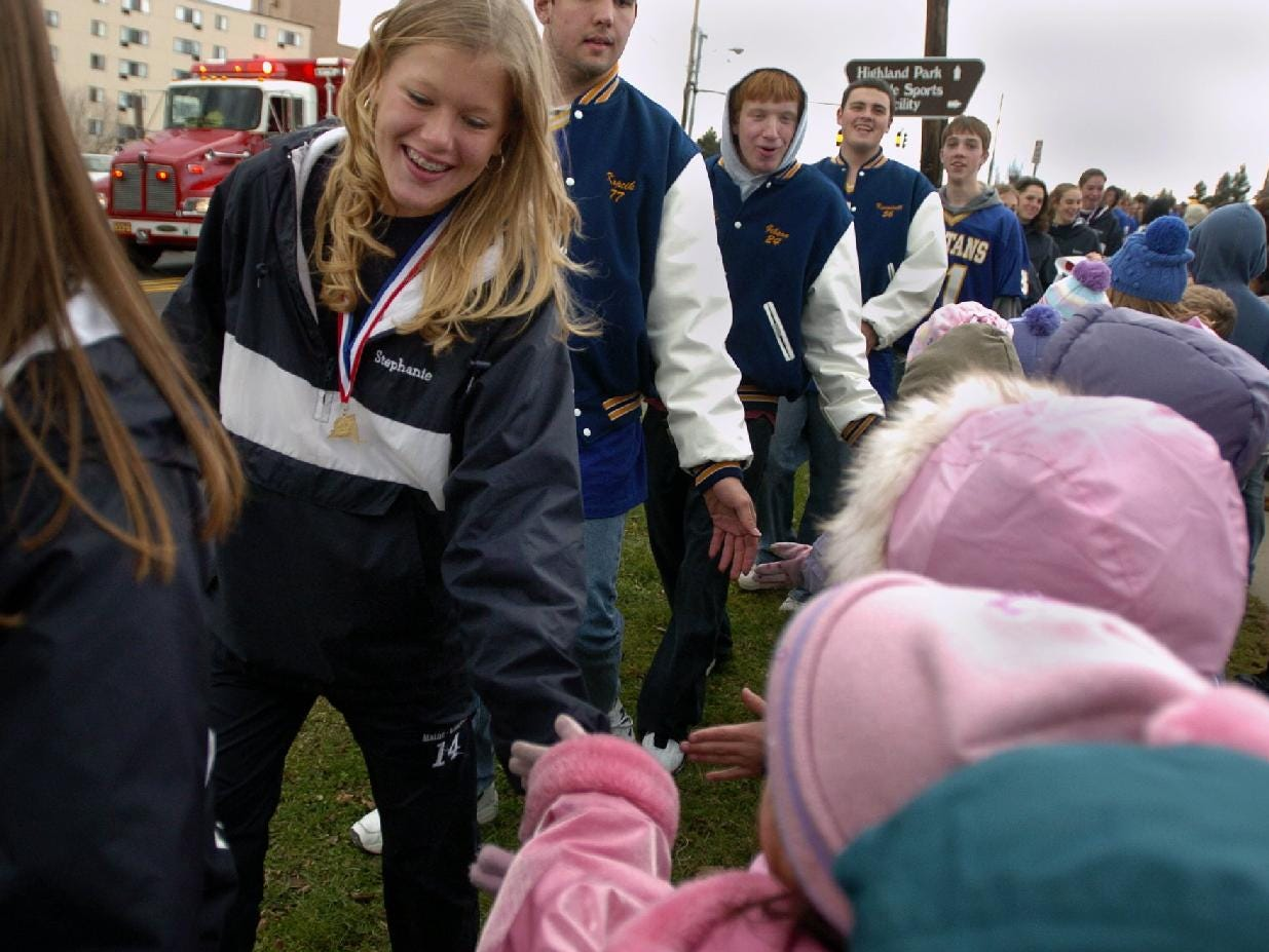 In 2004, Maine-Endwell Field Hockey player Stephanie Sanders along with her teammates greets students from Maine Memorial Elementary School along Hooper Road in Endwell during the parade honoring the state championship football and field hockey teams.