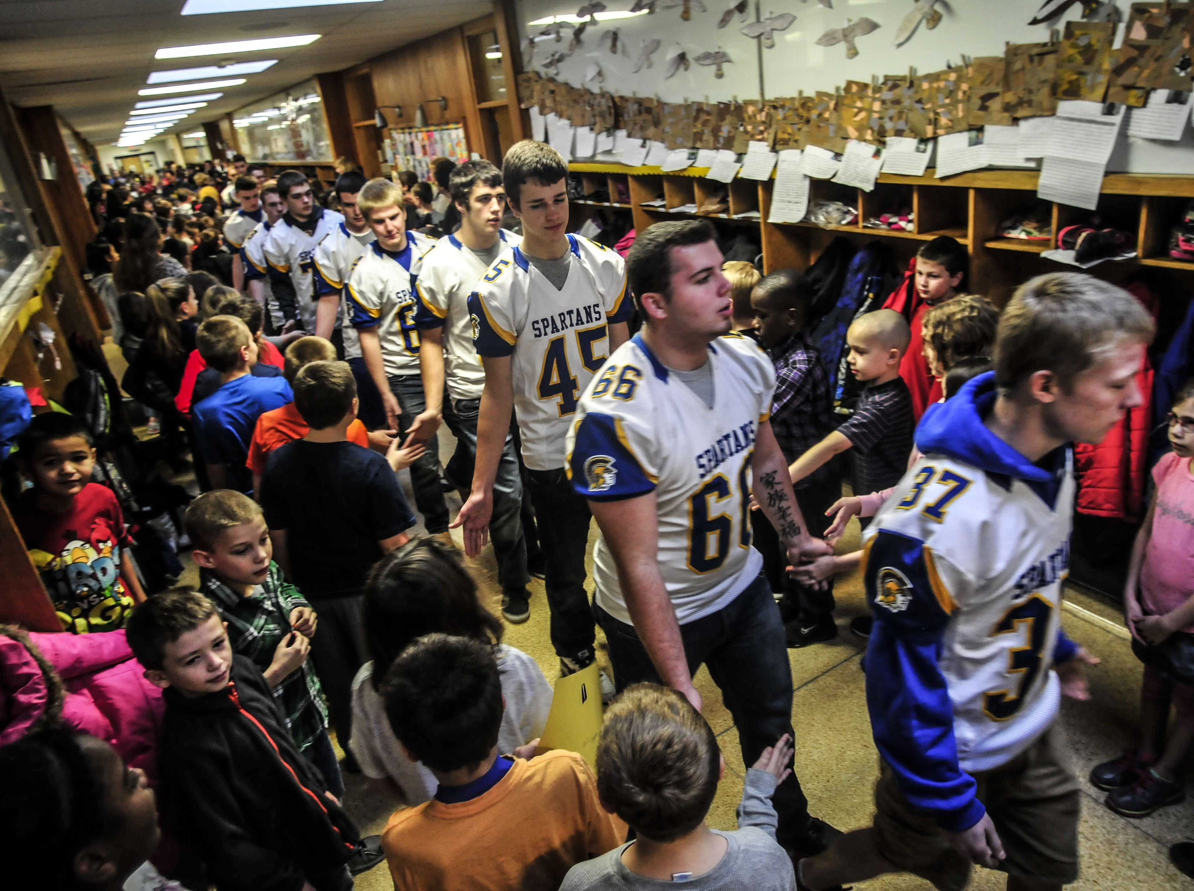 Spartan players went to each of the district schools for a parade through the hallways and classroom visits in recognition of their achievements after winning the Class B state championship for their third consecutive title in 2013.
