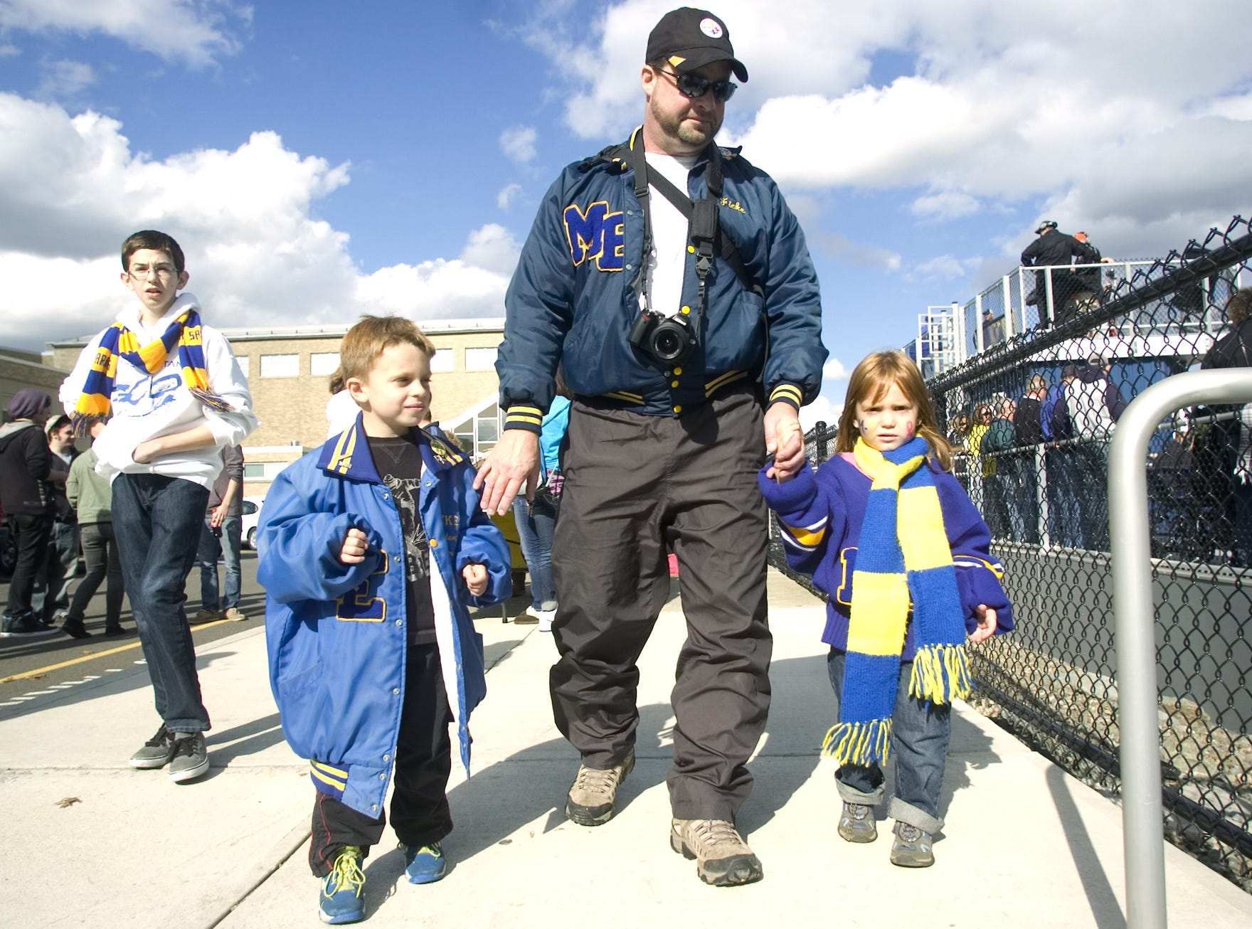 Maine-Endwell High School Class of 1985 alumnus Tom Ficke guides his children, 5-year-old Logan Ficke, left, and 4-year-old Ruby Ficke, to their seats prior to the start of the 2012 homecoming game against Union-Endicott, held at Spartan Stadium, in Endwell.