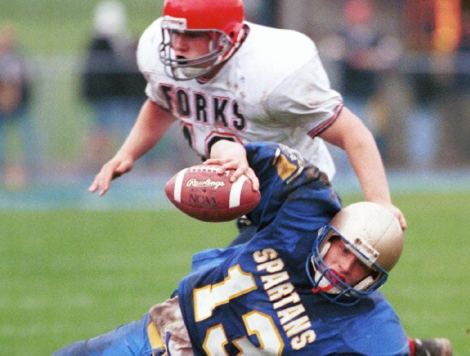 Maine Endwell quarterback Ryan Carney (13) loses his footing on the muddy ME football field during a 1998 game against Chenango Forks.