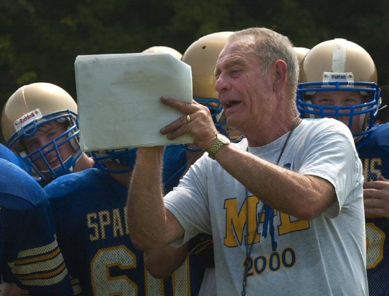 In 2003, Maine-Endwell head coach Dick Russ goes over offensive plays with his team during practice.