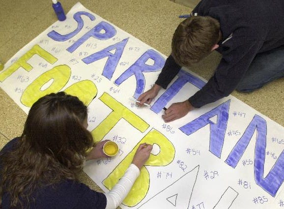 "In 2004, Maine-Endwell seniors Sarah Kane, left, and her twin brother, Dave, combine efforts to complete a banner that will be hung in the Carrier Dome in Syracuse during the football team's Class A semifinal game against Iroquois. Dave, a varsity football player, says the support of the school ""helps get the whole team going."""