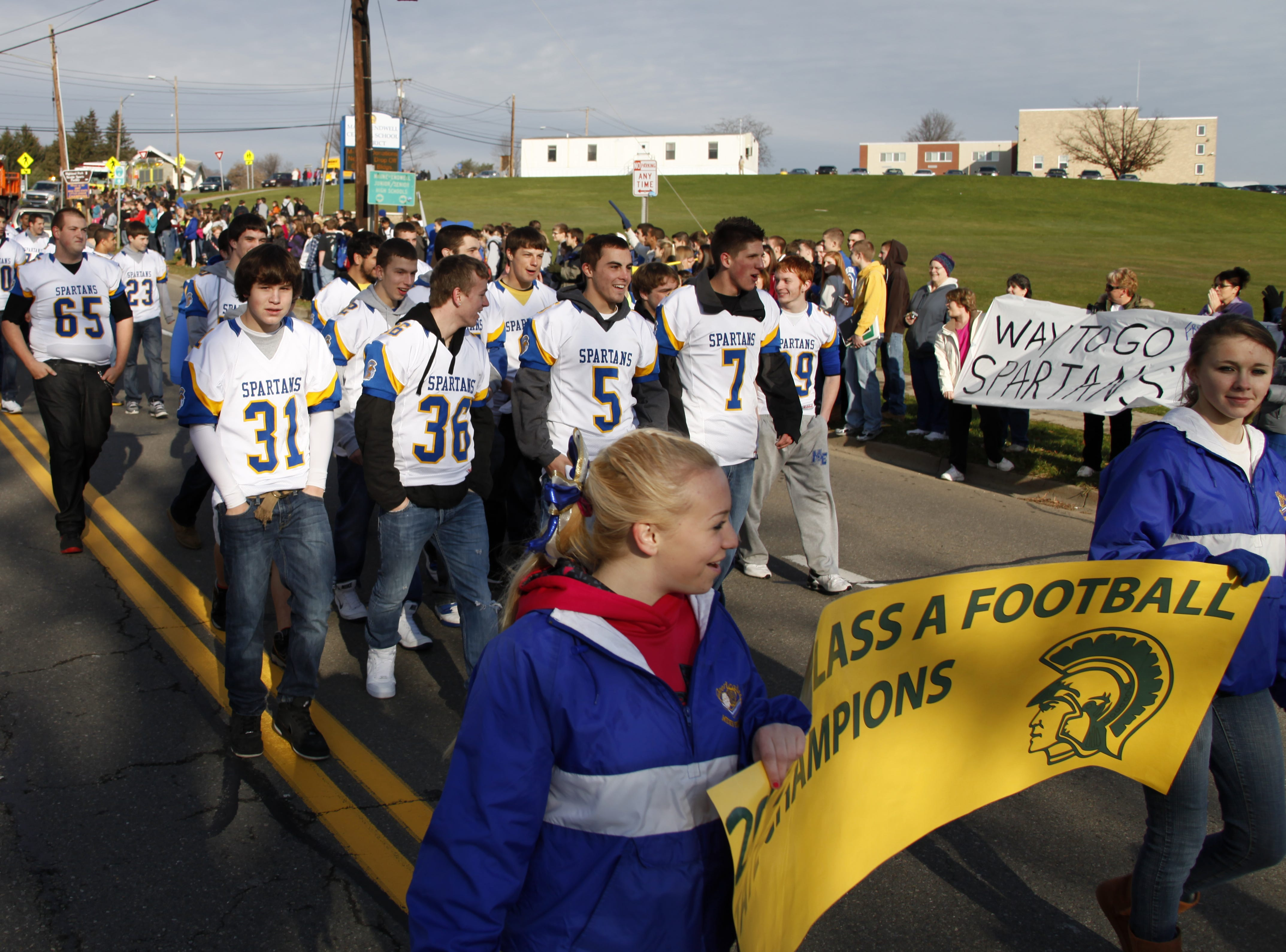 Students of Maine Endwell schools and members of the community line the streets of Hooper Road and Farm to Market Road in 2011 to observe the parade held for ME High School's Fall athletic teams that participated in state competitions.