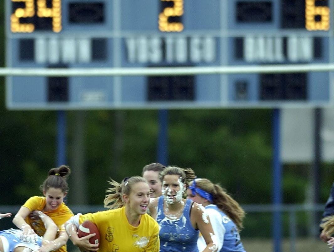 "Senior Hayley Hall runs for a long gain during the second half of the Maine-Endwell High School ""Reversal Game"" in 1999, where senior girls play a game of flag football with the junior girls, and the boys assume the role of cheerleaders."