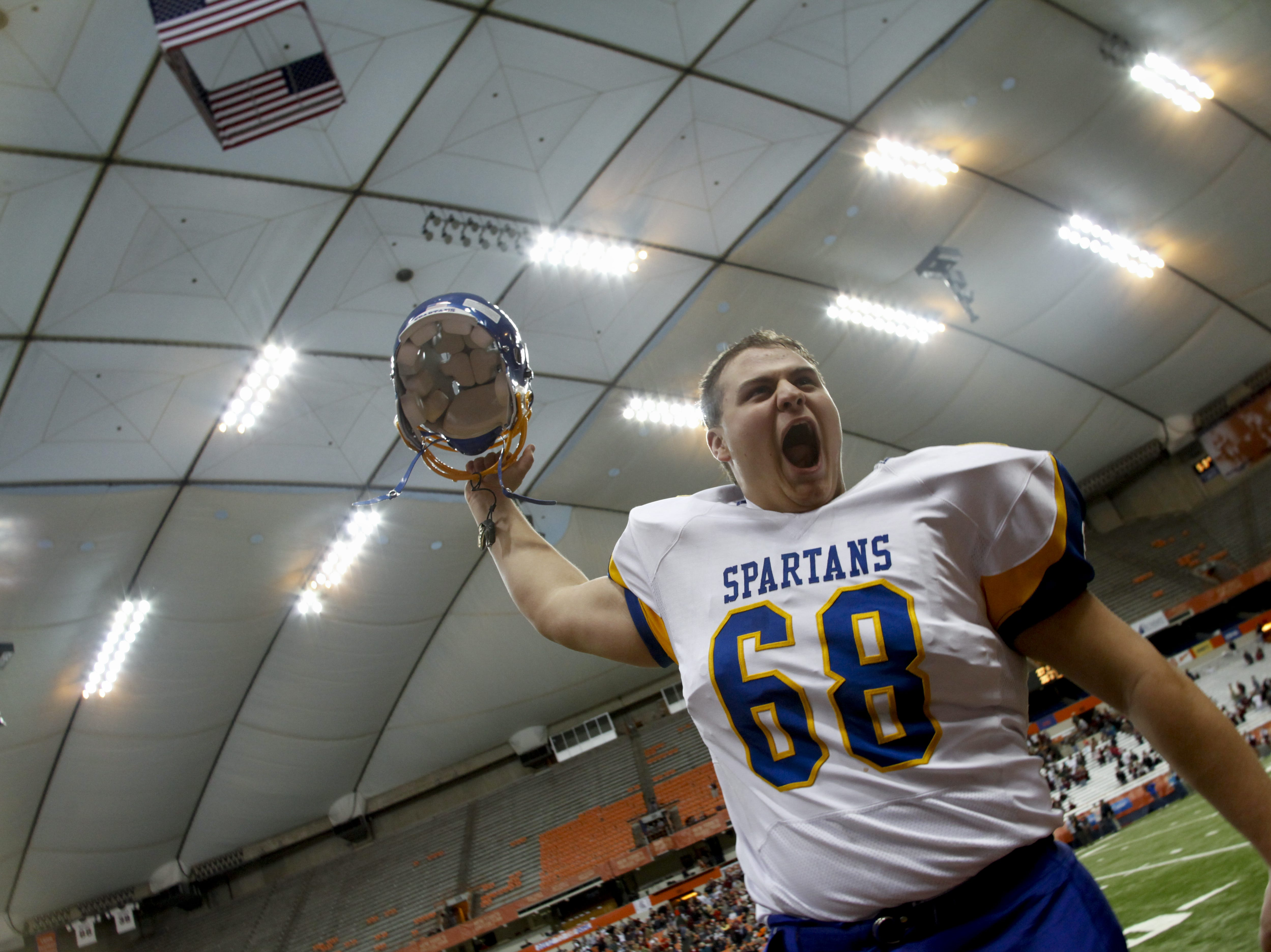 Maine Endwell's Heath Ferris throws his helmet up in celebration of his team's victory over Burnt Hills-Ballston Lake at the Class A New York State High School Football Championship held at Syracuse's Carrier Dome.