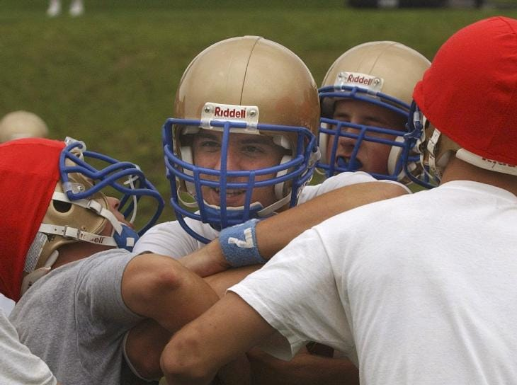 In 2004, Maine-Endwell running back Mike Meta runs into a wall of his teammates as M-E HS FOOTBALL practiced their offense during practice recently.