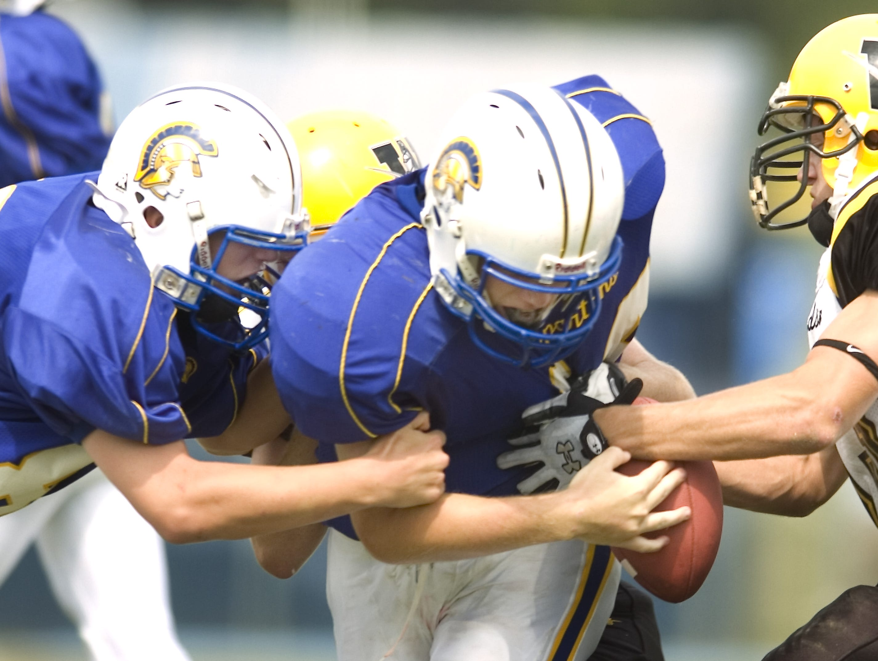 Adam Rosenbarker, left, of Maine-Endwell and his teammate Nathan Reynolds, in 2007, as Josh Quinn of Windsor strips the football away in the first quarter at Maine-Endwell High School.