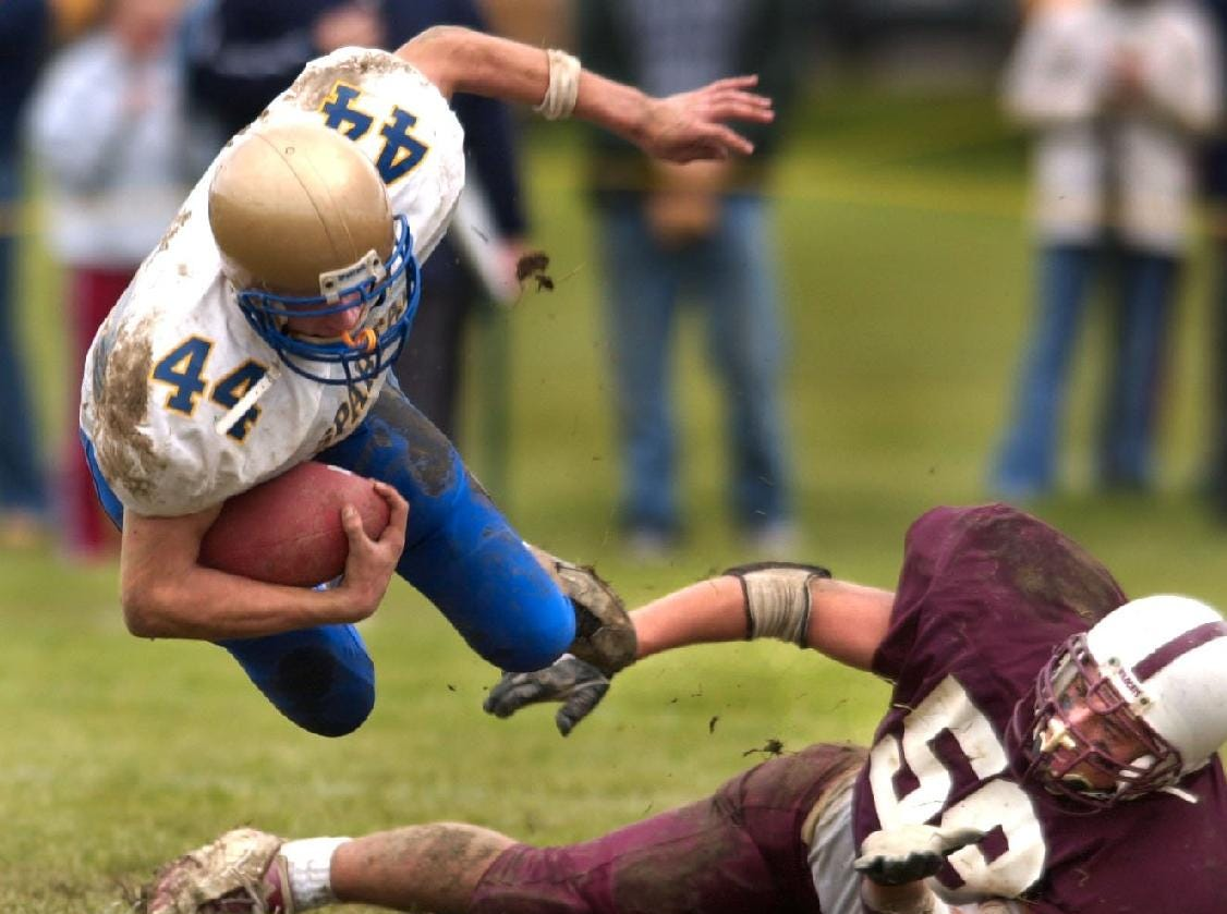 In 2001, Maine-Endwell's Adam Golden goes airborne after Johnson City's Mike DePersis upends Golden after reaching out and grabbing his foot in the first quarter at Green Field in Johnson City.