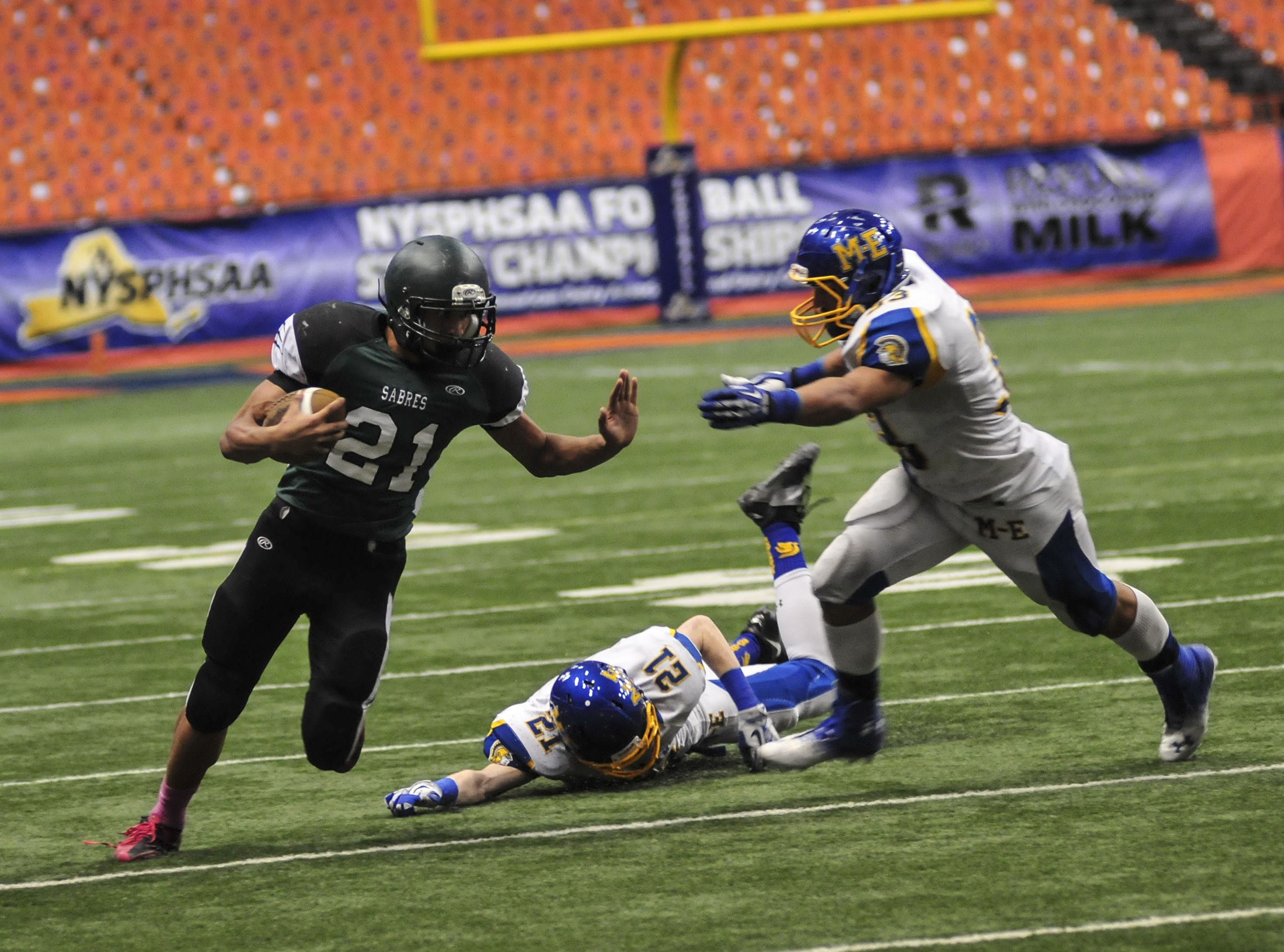 Schalmont's Devon Willis gets past Maine-Endwell's Michael Palmer but is tackled by Darnell Woolfolk during the 2013 New York State Public High School Athletic Association Football Class B Championship at the Carrier Dome in Syracuse on Sunday, Dec. 1.