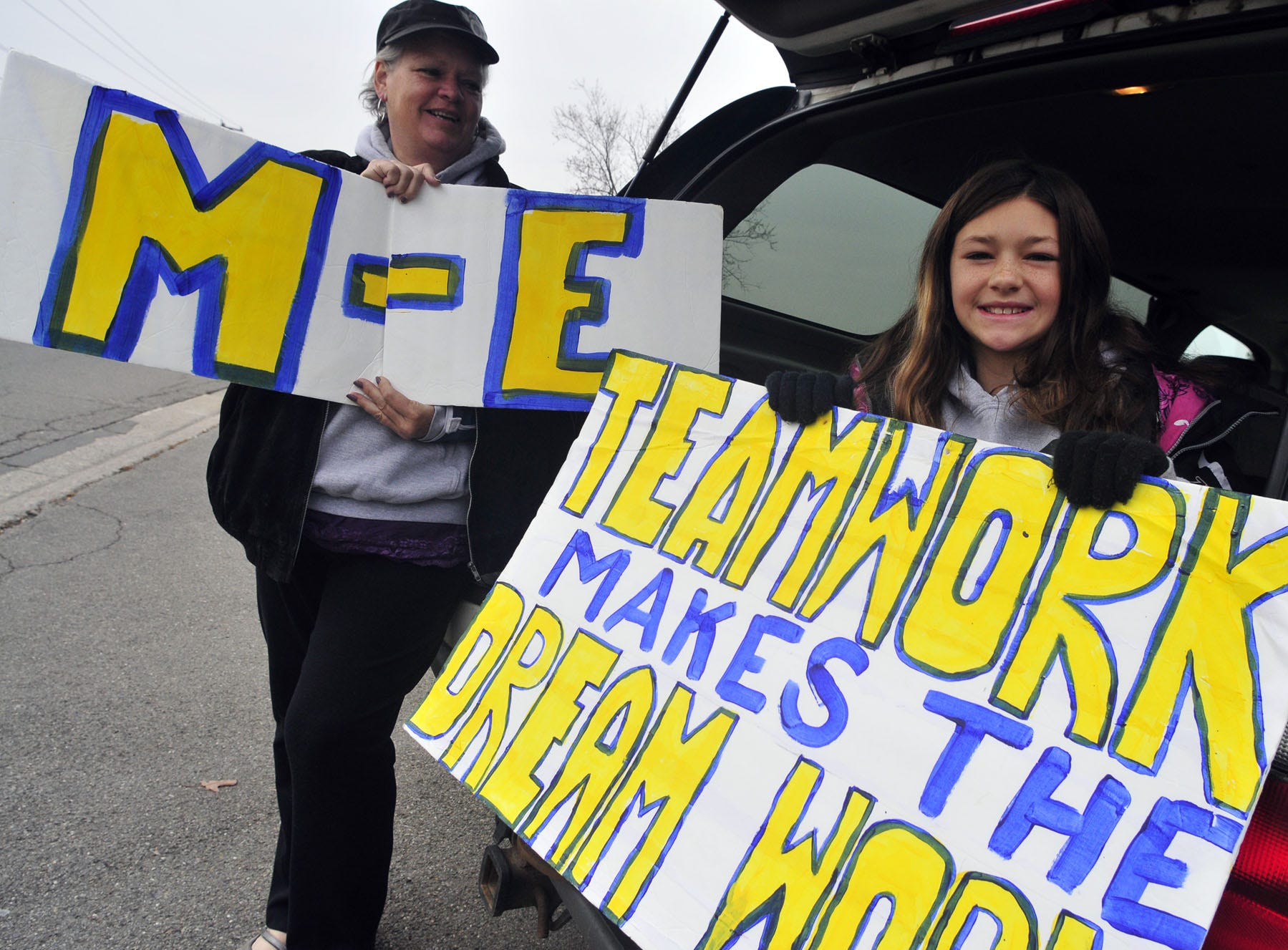 Laurie Mikels and her granddaughter Morgan Martin hold signs to cheer on the Maine-Endwell football team during the parade of champions on Friday Nov. 30, 2012.