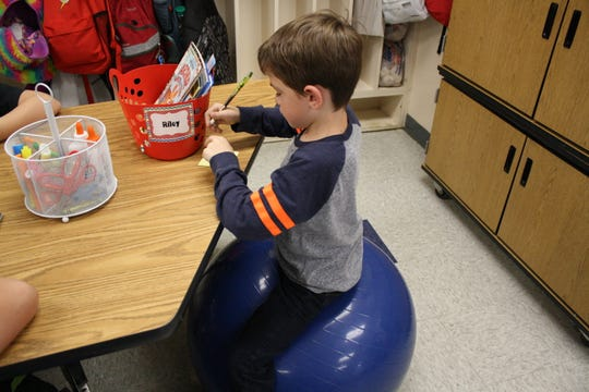 Riley Hayes, 7, completes a reading assignment while sitting on a yoga ball in Jessica McBreen's classroom at Chenango Forks Elementary School in Binghamton on Oct. 26.