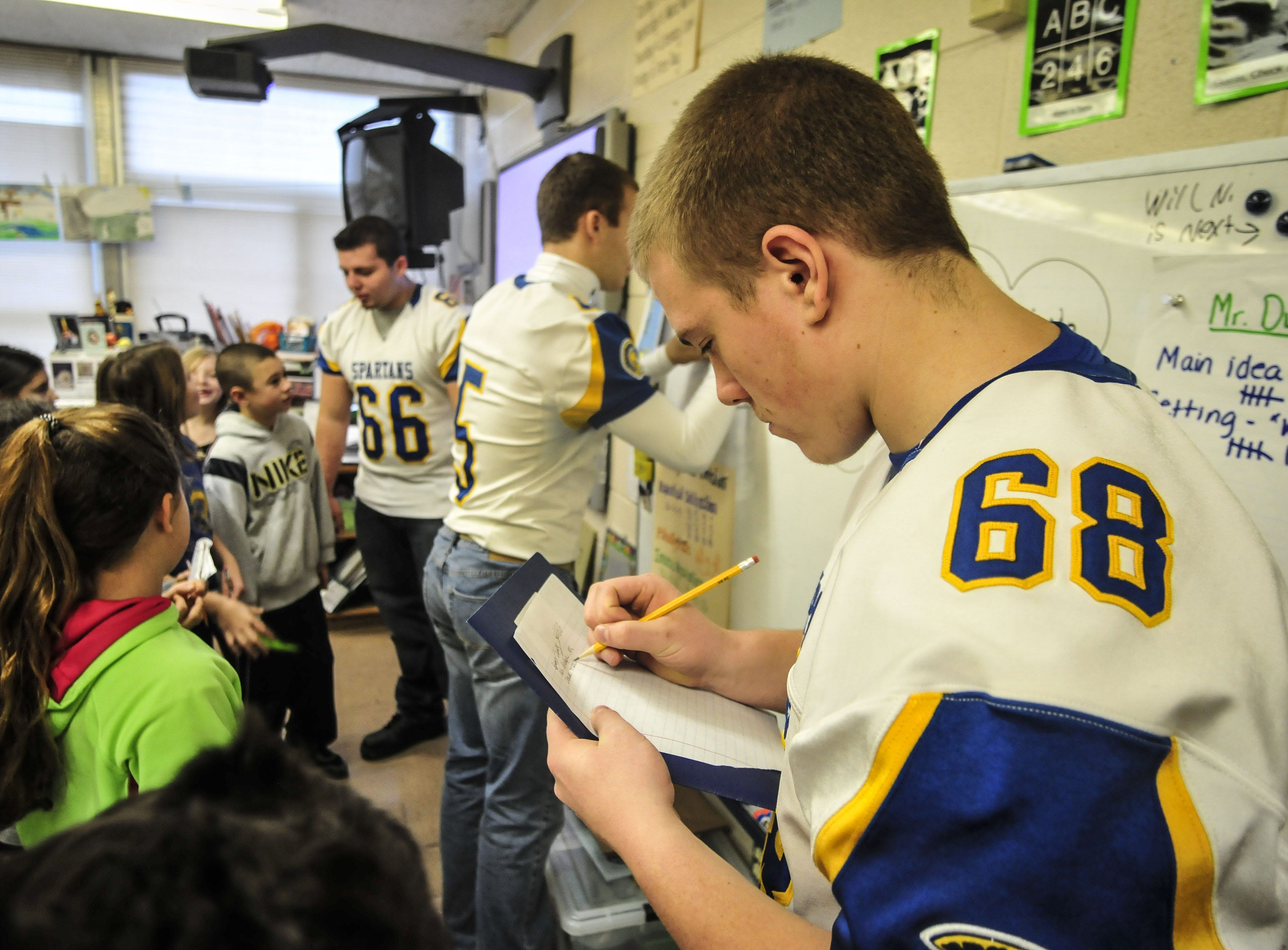 Chace Martino, a member on the 2013 Maine-Endwell football team, signs an autograph for Frankie Natale, 9, fourth-grader at Homer Brink Elementary School, as players enter the class room to give students words of advice.