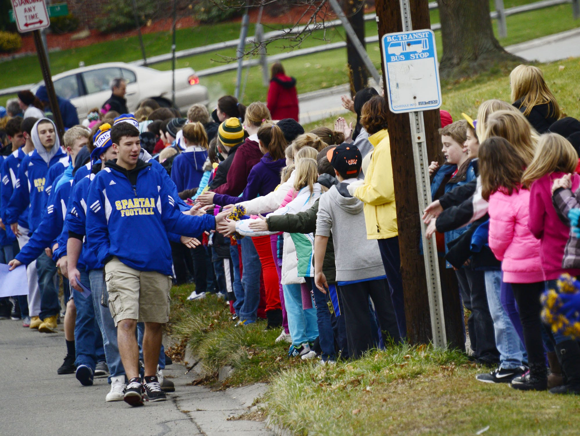 Members of the 2012 Maine-Endwell football team high fives fellow students as they walk towards downtown Endwell during a parade of champions.