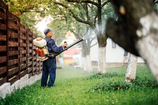Farmer Worker Spraying Pesticide Treatment On Fruit Garden