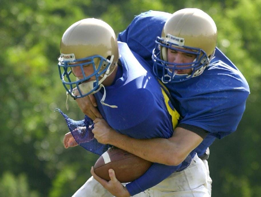 In 2001, Maine-Endwell's Matt Brown tackles Mike Tarbox during drills at practice.