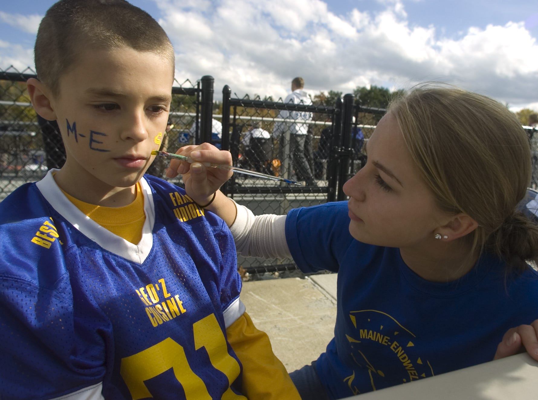Nine-year-old Josiah Kendrick has his face painted by Maine-Endwell High School senior Jamie Pastrick prior to the start of the 2012 homecoming game.