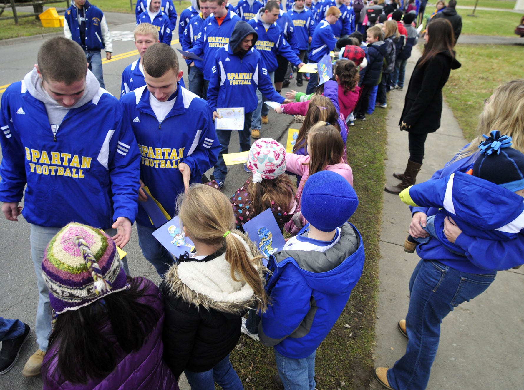Members of the Maine-Endwell football team high fives fellow students as they walk towards downtown Endwell during a 2012 parade of champions.