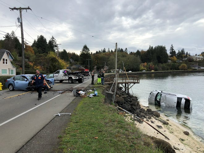 Crews remove a Dodge car from the shores of Sinclair Inlet Friday afternoon following a head-on crash on Beach Drive near the Annapolis dock.