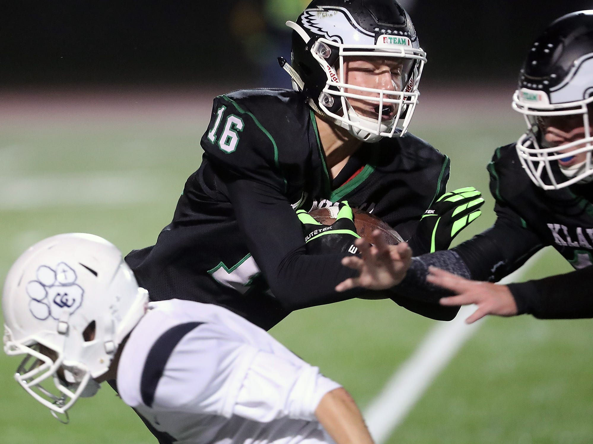 Klahowya's Andrew Dickson (center) carries the ball as teammate Hunter Wallis (right) makes a grab for Cascade Christian's Quinn Greiner (left) during the second half of their game at Silverdale Stadium on Thursday, October 25, 2018. Dickson ran the ball into the end zone for a touchdown on the play.