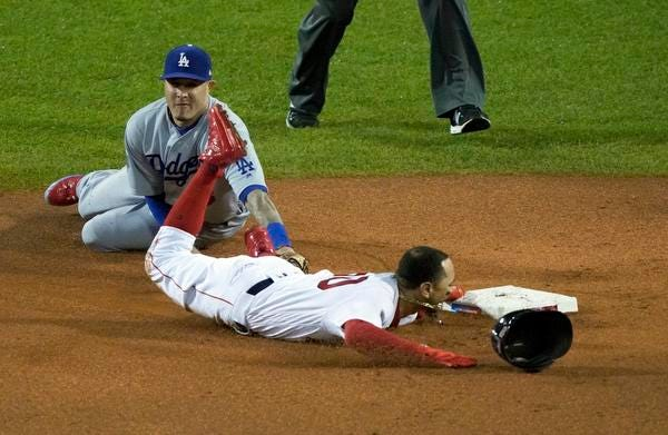 Boston Red Sox's Mookie Betts steals second base past Los Angeles Dodgers shortstop Manny Machado, left, during the first inning of Game 1 of the World Series baseball game Tuesday, Oct. 23, 2018, in Boston.