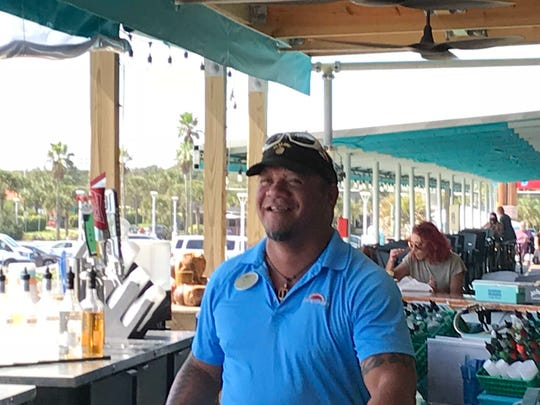 Awai Ku'ualoha, a bartender at the Cocoa Beach Pier, is all smiles about a recent pay boost.
