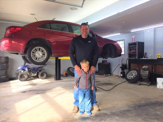 Jeffrey Bessinger and his 4-year-old son, Max, stand inside their new Bucyrus auto dealership, known as Woody's Rides.