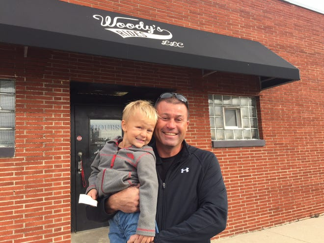 Jeffrey Bessinger and his 4-year-old son, Max, stand outside their new Bucyrus dealership, known as Woody's Rides.