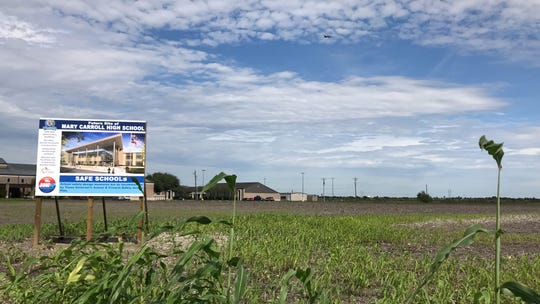 Two signs announcing the site of the new Carroll High School are set near a field on Saratoga Boulevard. One sign is next to a convenience store near Saratoga Boulevard and Weber Road, and another is near Most Precious Blood Catholic Church on Saratoga Boulevard.