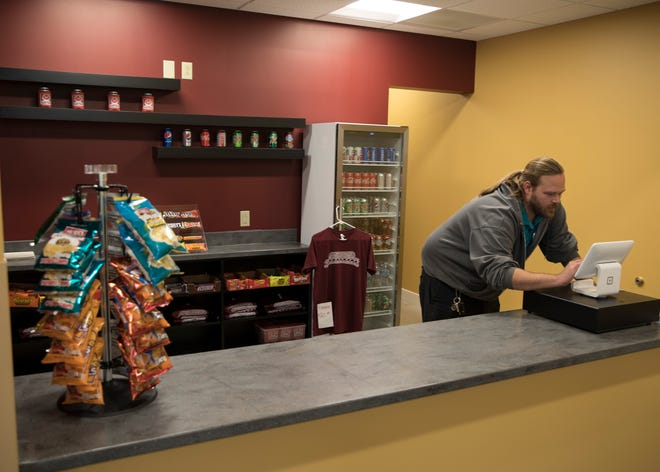 Gene Betts, secretary for the Majestic board, works with the register system in the new Majestic Theatre concession area.